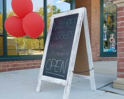 "Sign reading ""Now Open"" in front of store"