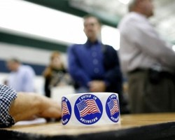 Voting stickers on table at voting precinct with people in line in background