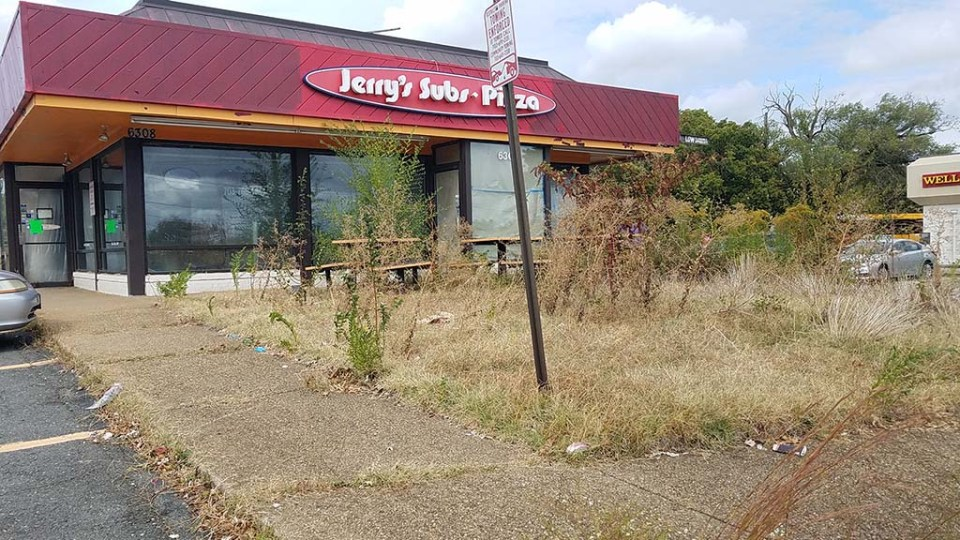 Jerry's from the front, with overgrown grass and trash visible
