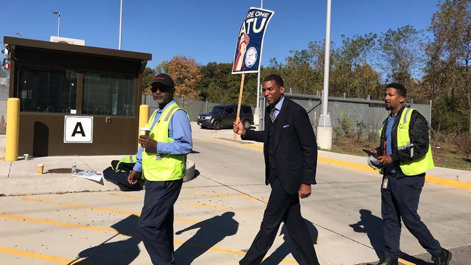 Rodney Lusk marches with two workers. All are holding signs.