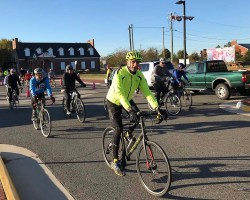 Dan Storck leading a group of riders down a street on his bike