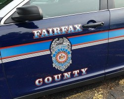 The drivers side door of a Fairfax County Police cruiser with the department's shield on it.