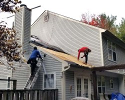 Workers on roof of house