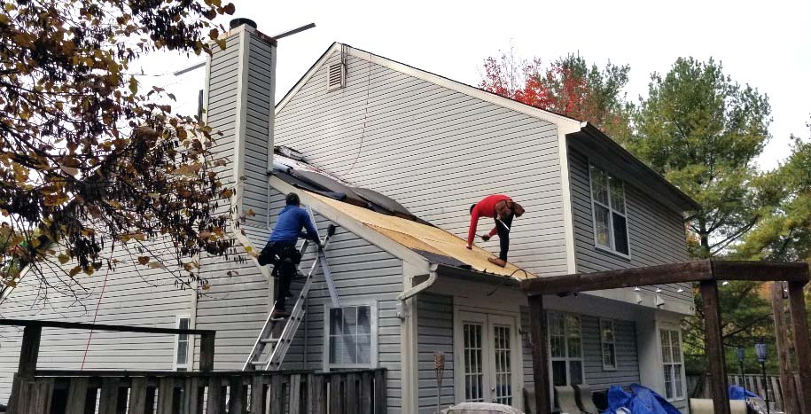 Two workers on roof of house