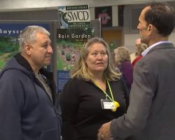 Screenshot from video in article, it shows Dan Storck talking to man and woman at last year's Expo