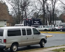 Gray van in foreground and police van in background near garden style housing