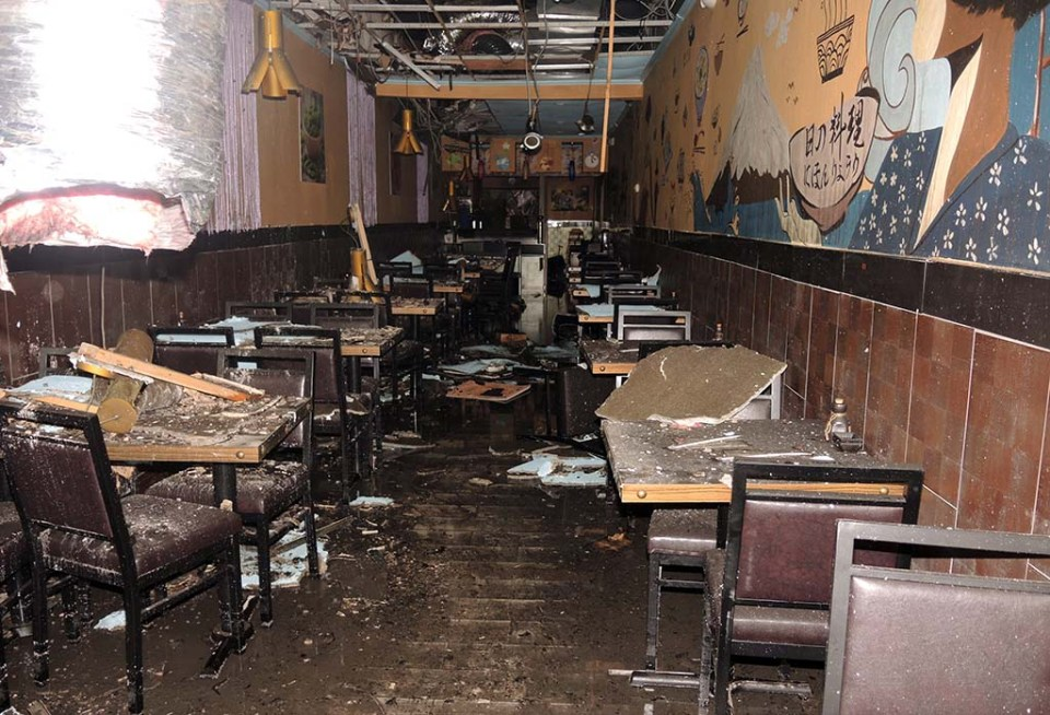 Chairs and tables with pieces of ceiling on them, various debris in the narrow dining area of restaurant