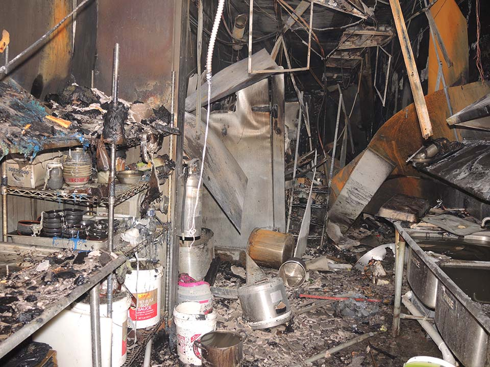 Interior of kitchen with damaged metal hanging and destroyed cooler in center