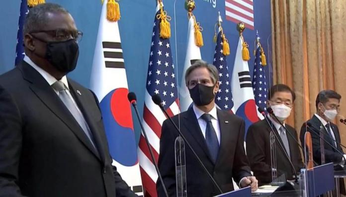 A group of people standing in front of flags  Description automatically generated with low confidence