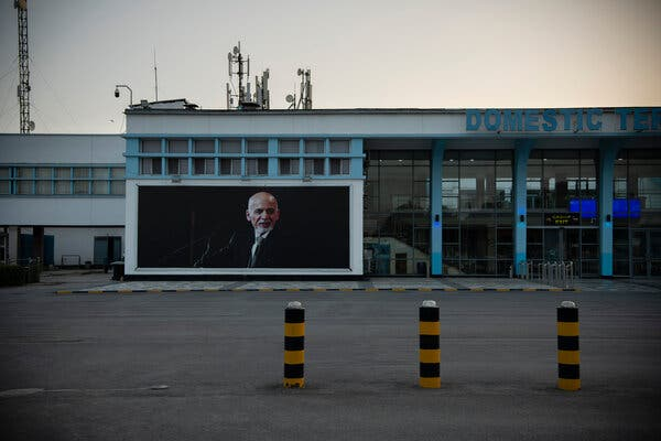 A poster of Ashraf Ghani outside the deserted domestic terminal at the airport in Kabul on Sunday morning.