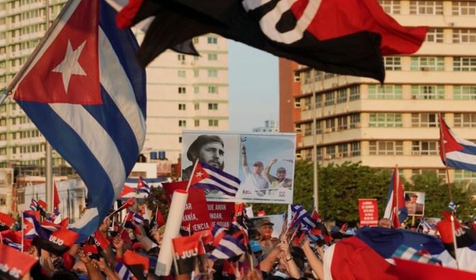 La gente lleva un cartel con fotografías del fallecido presidente de Cuba, Fidel Castro, el presidente y primer secretario del Partido Comunista de Cuba, Miguel Díaz-Canel, y el ex presidente y primer secretario del Partido Comunista de Cuba, Raúl Castro, durante un mitin en La Habana, Cuba, el 17 de julio. 2021. REUTERS / Alexandre Meneghini