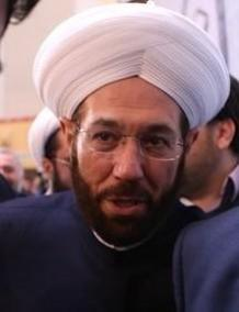 A person wearing a white turban  Description automatically generated with medium confidence