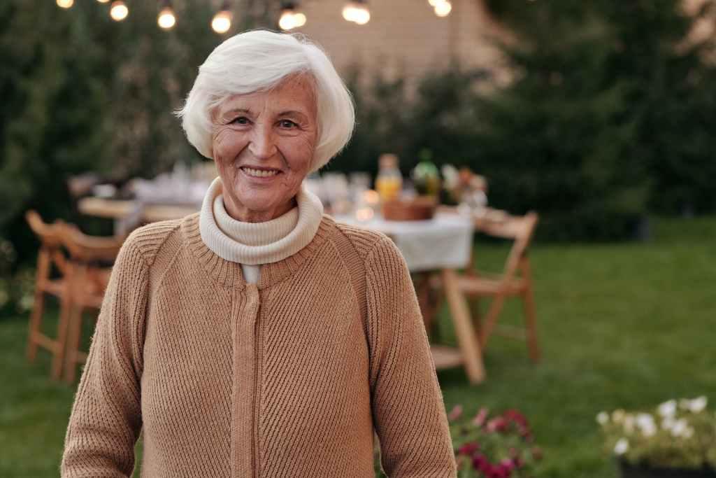 cheerful senior woman smiling in backyard