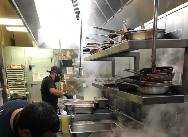 Two people wearing aprons work in a stainless-steel kitchen with steam rising from the grills.