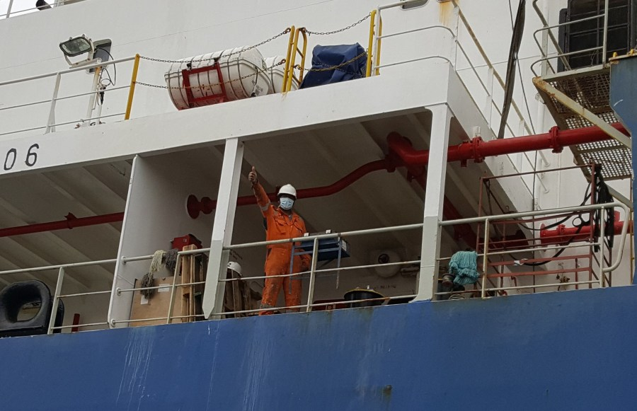 A photo of a Delaware seafarer on a ship, giving a thumbs up