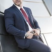 Handsome male escort in dark grey suit leaning against a building