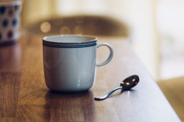 Photo of white mug of tea with teaspoon on wooden kitchen surface whilst considering to try hypnotherapy for anxiety depression stress mistakes