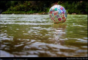 "A ""get well soon"" balloon floats in the contaminated waters of the Animas River flowing through Durango on Monday afternoon August 10, 2015 -- photo The Durango Herald, Shane Benjamin"