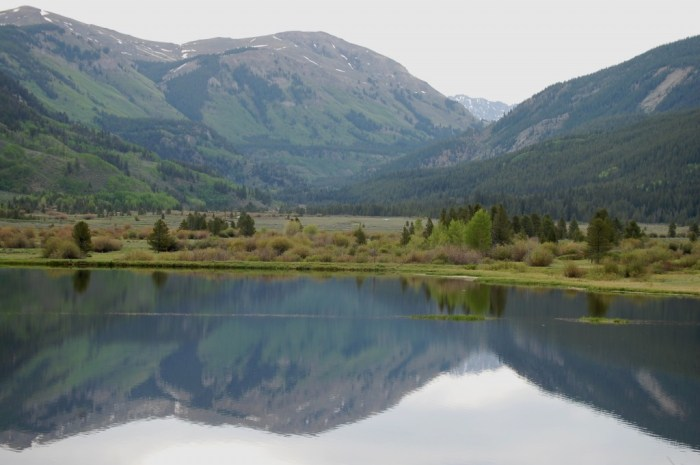 Mountains reflect off of Bolts Lake as seen from US 24 S in Colorado. Photo via  LessBeatenPaths.com.