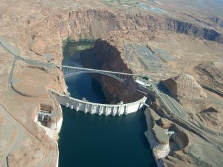 Seen from the air, Glen Canyon Dam holds back the Colorado River to form Lake Powell. The state of Colorado is looking into how to fund a program that would pay irrigators to reduce their consumptive use in order to send water downstream to a savings account in Lake Powell. Photo credit: Brent Gardner-Smith/Aspen Journalism