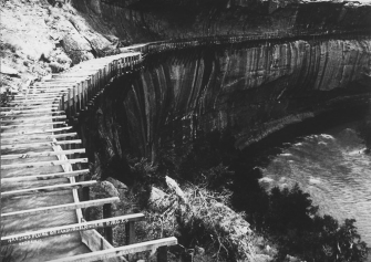 Hanging flume on the lower San Miguel River in 1891. Remnants of the flume may still be seen today. By illegible - https://westernmininghistory.com/2252/an-engineering-marvel-colorados-hanging-flume/, Public Domain, https://commons.wikimedia.org/w/index.php?curid=97062338