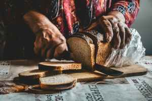 close up shot of a person slicing a bread on a wooden chopping board