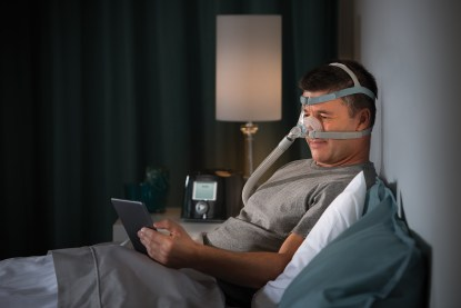 Male Reading with CPAP Machine