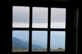 Summit of Mt. Washington, NH, and surrounding ridges, through window of Tip Top House