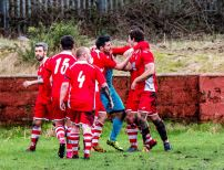 Players celebrate with Jarrad Howells following his added time penalty save.
