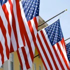 American Flags lined up against a yellow building