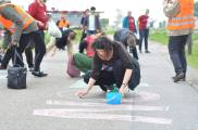 """Chalking """"MIGRATION IS NOT A CRIME"""" outside the detention center by Amsterdam"""