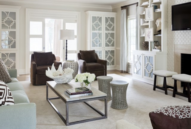 Living room with sea foam sofa, brown armchairs, wire frame stools, a white painted brick fireplace with a wall mounted TV in the mantel, white cabinets with sea foam inlets and a sliding door