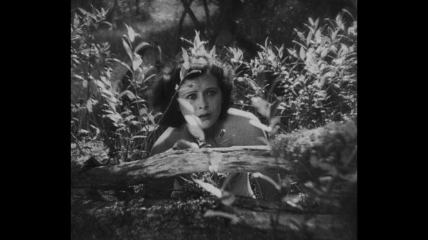 Still from Gustav Machaty's film Extase: Eva hiding behind bushes