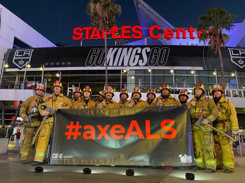 Firefighters pose with vinyl banners in front of the Staples Center.