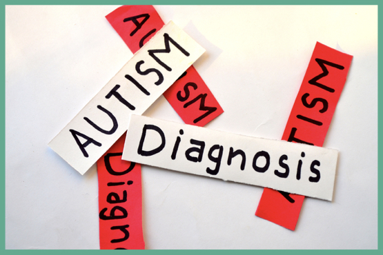 Image of red and white paper cut outs labelled with the words autism and/or diagnosis