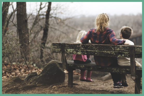 Image of a mother sittings on a bench in the forest with her two children (one small blonde girl, and one brown-haired boy)
