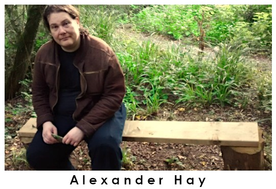 Alexander Hay, Research Communication and Engagement Officer at CRAE, sitting on a bench in some woods.
