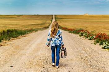 A young woman, back turned to viewer, says goodbye and begins a long journey on a dirt road. CRAE logo on right. Original image by Jose Antonio Alba, c/o Pixabay.com.