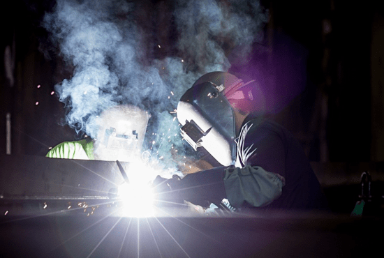 Welders light up the darkness with their blowtorches as they work on metal. CRAE logo on the right. Image by Pexels c/o Pixabay.com.