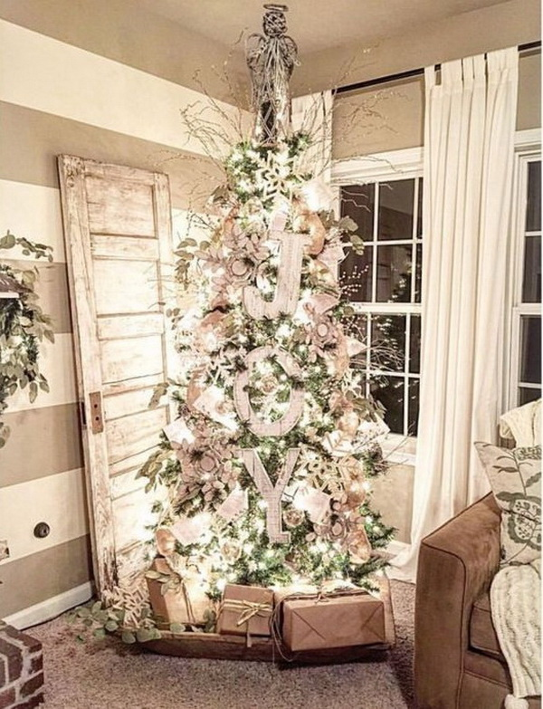 Rustic Christmas tree decorating with burlap, wooden JOY letters.