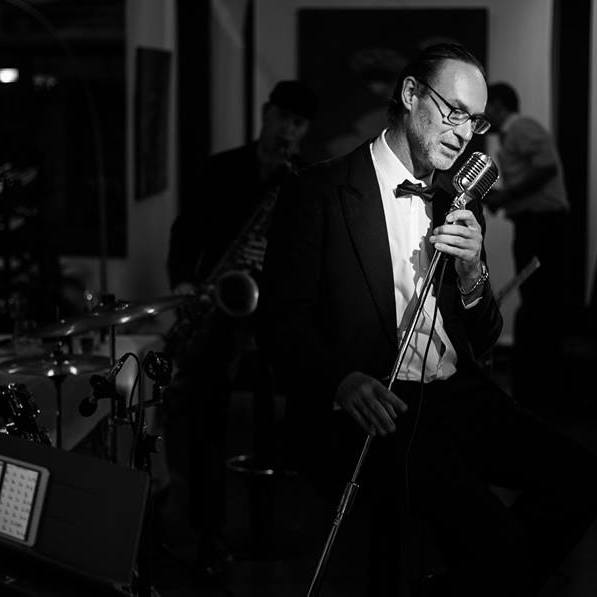 Heritage Suites Hotel luxury travel public relations case study - Thursday Jazz featuring male jazz singer with a jazz band. He's dressed in black tie ensemble with black tie, microphone in hand.