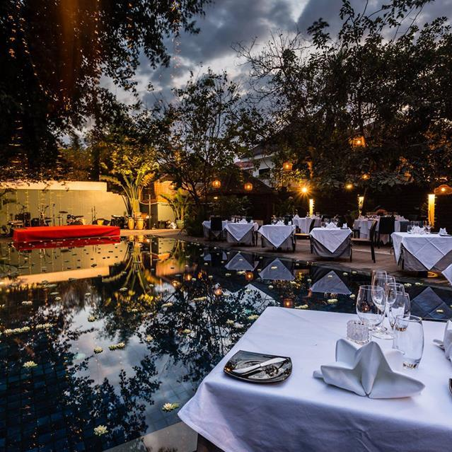Heritage Suites Hotel luxury travel public relations case study - dinner by the pool; formal white table cloths with tableware; red stage for Apasara dancers to perform on one end of the pool