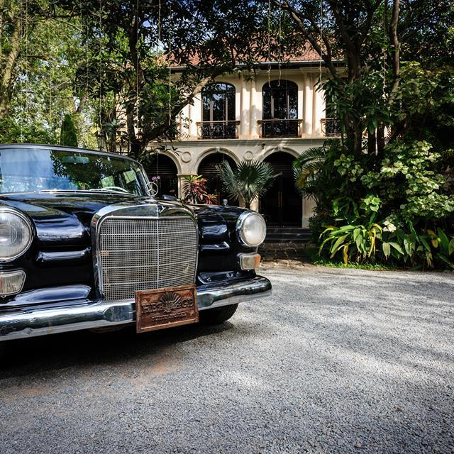 Heritage Suites Hotel luxury travel public relations case study - hotel's colonial facade and vintage Mercedes Benz car parked in front, with lots of greenery in the background