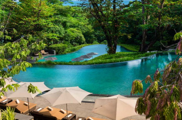 Staycation in Singapore at Capella - casacading pools resembling rice fields in Bali with lush greenery, deck chairs, parasols and towels. Minutes away from the sea.