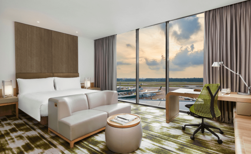 Staycation in Singapore at the Crowne Plaza Changi Airport Premier Room with Runway View - bed, chair, stool, lamps, chairs, business table and floor to ceiling window featuring runway views and aeroplanes