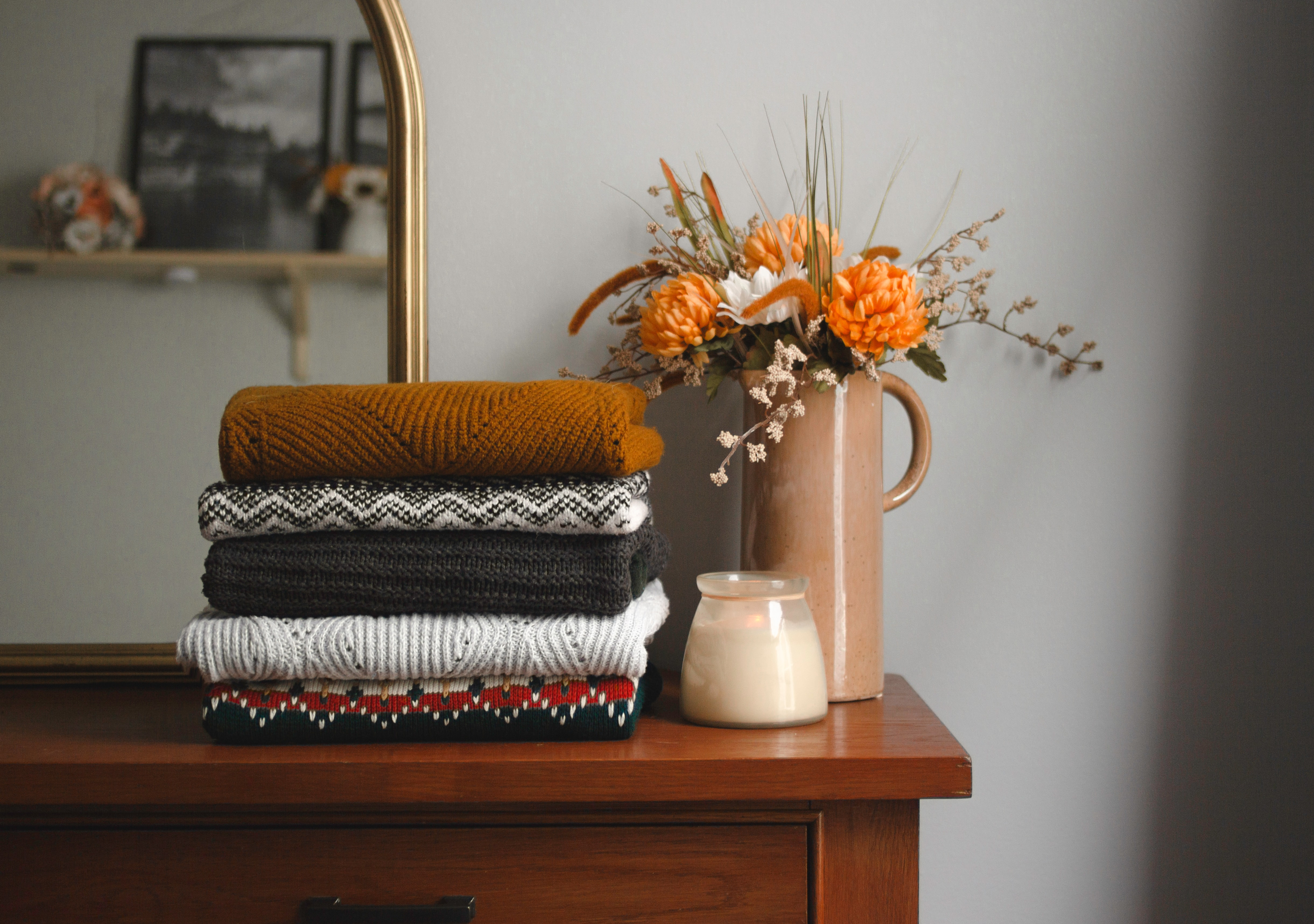 Sweater Stack with Flowers and Candle