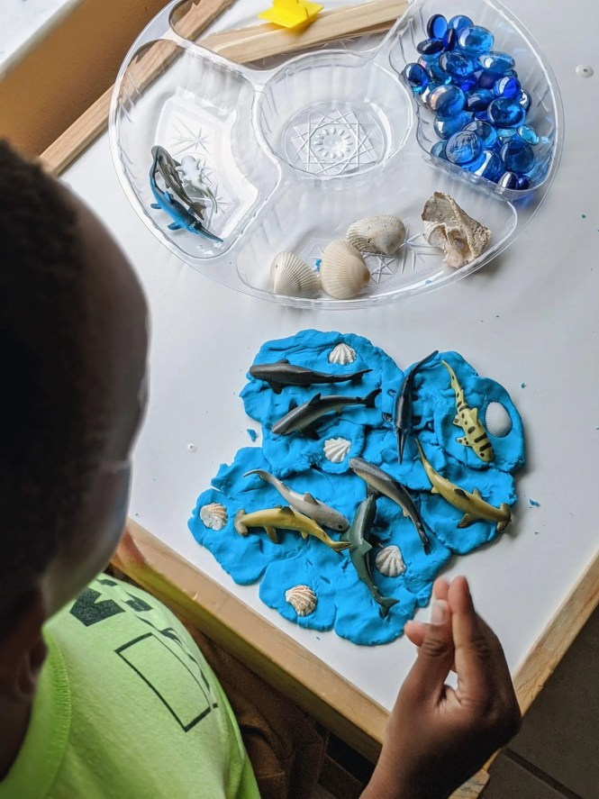 Black boy playing with blue play dough and sharks
