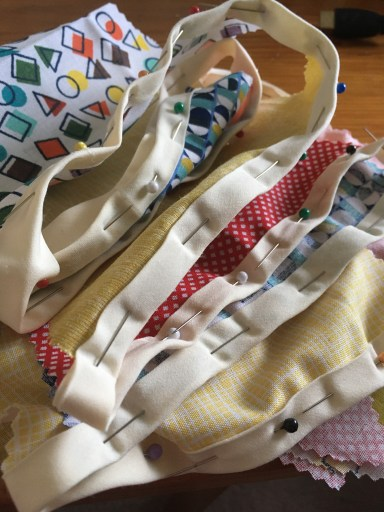 Bunting, brightly coloured fabric pinned and folded into a stack ready for sewing