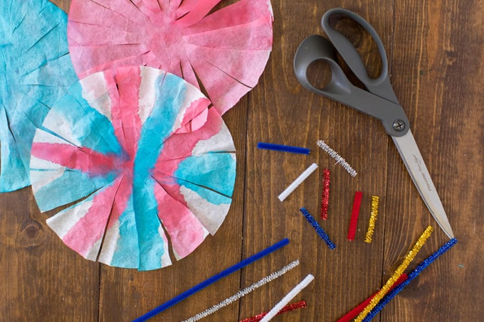 painted coffee filters and pipe cleaners on a table