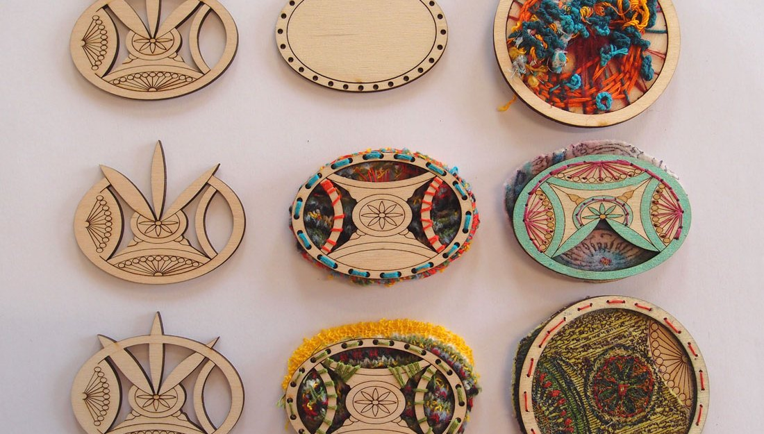 A selection of lasercut brooches made by participants with coloured yarn/thread weaved through.